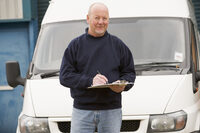 picture shows a man with a check list in front of a commercial van