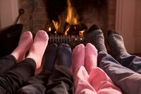 Photo shows the feet of a family in front of a fire
