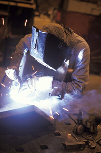 Photo shows a welder wearing protective clothing