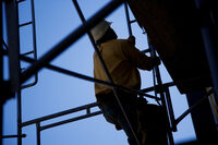 Photo shows a construction worker climbing a scaffold ladder