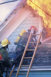 Photo shows firefighters dealing with a house fire