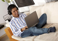 Photo shows a man using a laptop at home