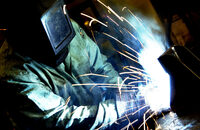 Photo shows a worker wearing personal protective equipment and clothing