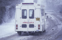 Photo shows an ambulance driving in the winter weather
