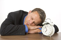 Photo shows a man in a suit sleeping by an alarm clock