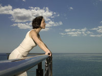 Photo shows a woman leaning on a balustrade