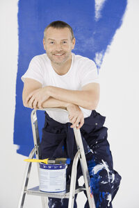 Photo shows a painter standing on a stepladder