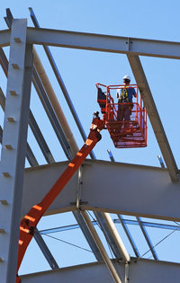 Photo shows a worker using a cherry picker to work at height
