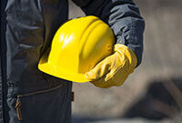 Photo shows a construction worker holding a hard hat
