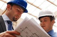 Photo shows two workers looking at blueprints