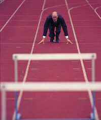 Photo shows a man in a business suit about to hurdle